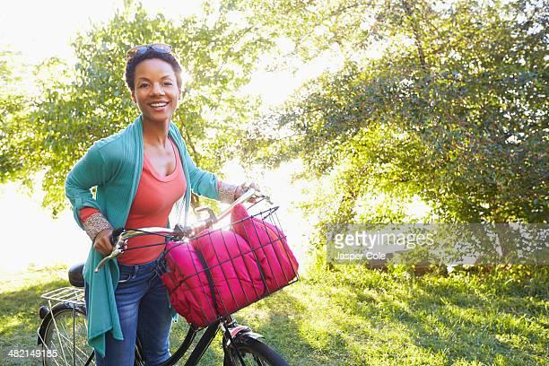 Black woman pushing bicycle outdoors