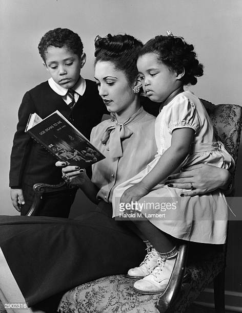 A Black woman sits and reads a religious children's book to a young boy and girl circa 1947