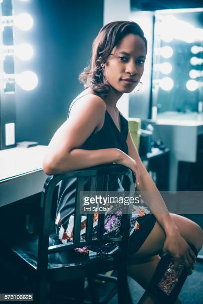 Black woman sitting at vanity mirror