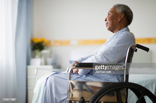 Black woman sitting in wheelchair in  hospital
