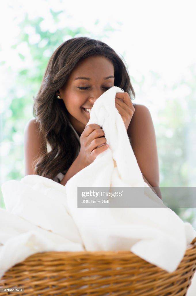Black woman smelling clean towels