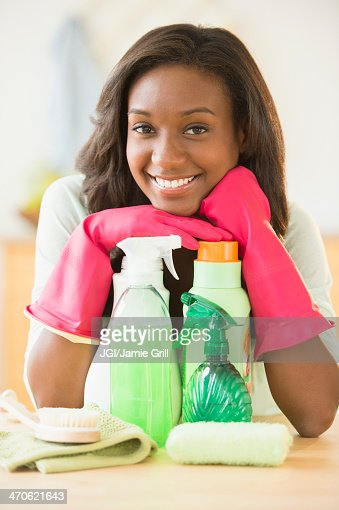Black woman smiling with cleaning products : Stock Photo