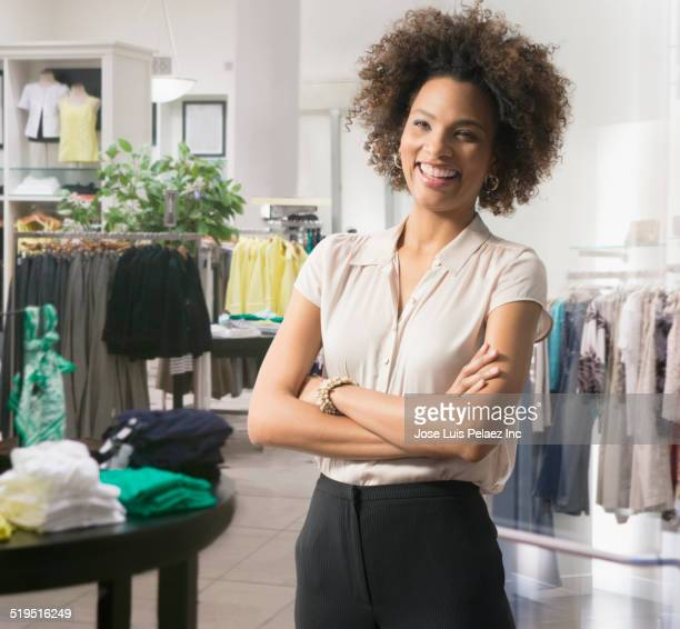 Black woman standing with arms crossed in clothing store