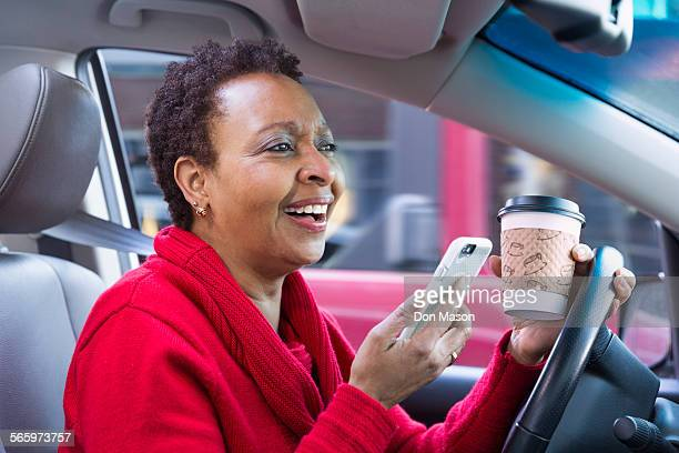 Black woman using cell phone and drinking coffee while driving car