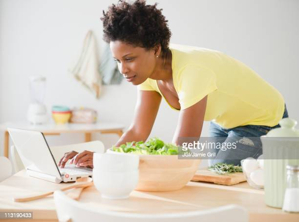 Black woman using laptop on dining room table