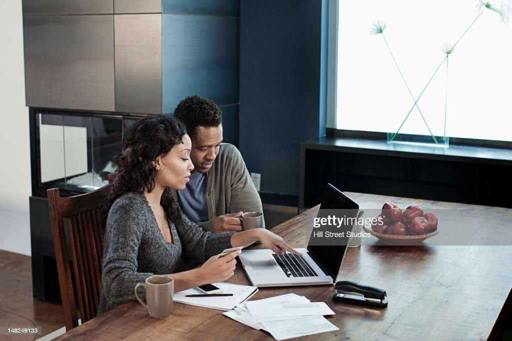 Black woman using laptop while husband drinks coffee