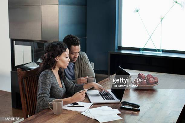 Black woman using laptop while husband drinks coffee