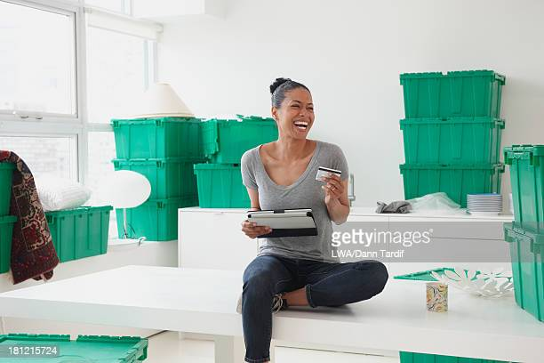 Black woman using tablet computer in new house