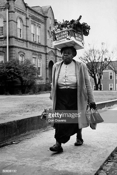 Black woman w National Bohemian beer box loaded w turnip greens balanced on her head walking on sidewalk during bus boycott protesting policy of...
