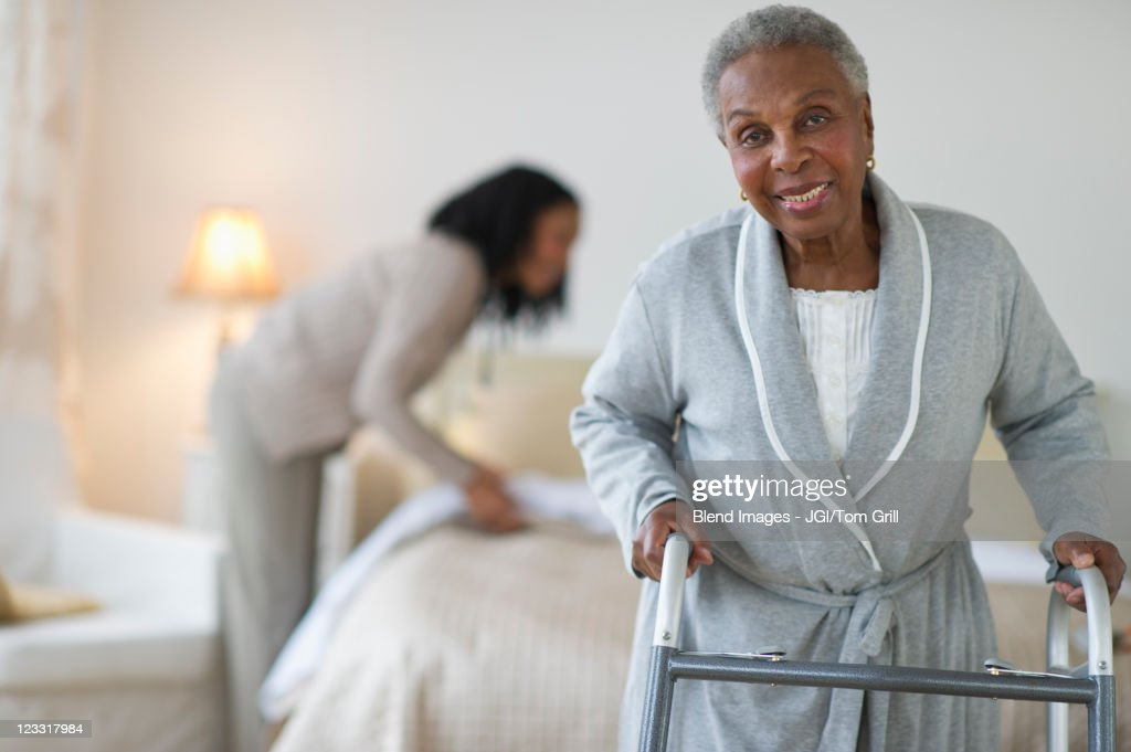 Black woman walking with walker in bedroom