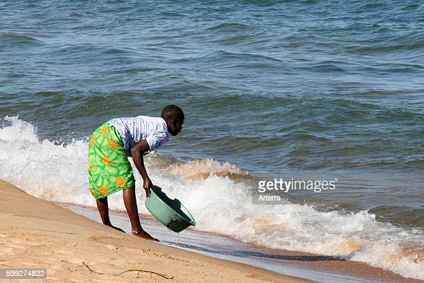 Black woman washing the laundry on the beach along Lake Malawi Malawi Africa
