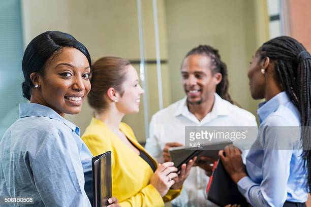 Black woman with group of business people smiling