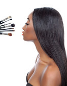 Black woman with straight hair and makeup brushes isolated on white