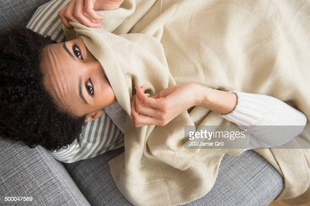 Black woman wrapped in blanket on sofa