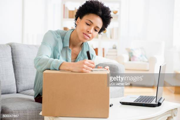 Black woman writing address on package