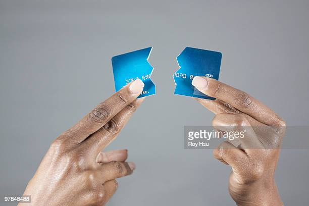 Black woman's hand holding broken credit card