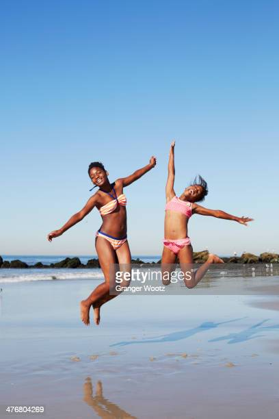 Black women jumping for joy on beach