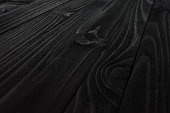 Black Wood Texture close-up. Shield from diagonally directed boards with wavy pattern of fibers.
