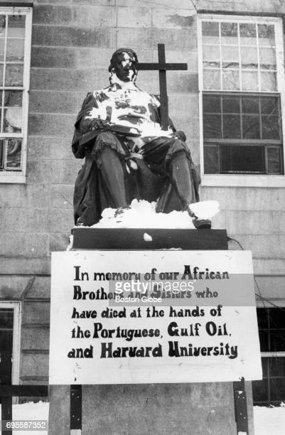 A black wooden cross sits in the snow behind a statue of John Harvard in Harvard Yard at Harvard University in Cambridge Mass on March 6 1972...