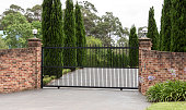 Black metal driveway entrance gates set in brick fence with pine trees in background