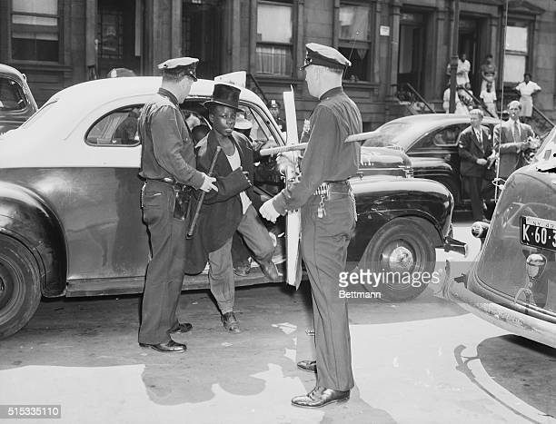 A black youth is escorted out of a police car one of 360 held in connection with looting and rioting in Harlem on August 2 1943 Where the top hat...