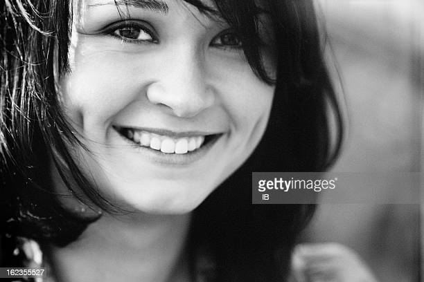 Black-and-white portrait of a charming laughing girl