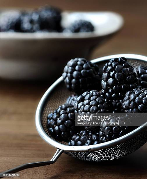 blackberries in a sieve, bowl in the background