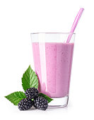 blackberry milkshake with straw in glass and fresh ripe berries near isolated on white background. Healthy drink