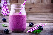 blackberry smoothie in a mason jar on a wooden rustic background