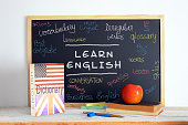 Blackboard in an English class. American and British English. Some books and school stuff for studying English language in a classroom.