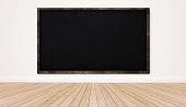 Blackboard on white wall with wood floor, empty classroom