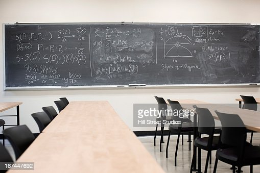 Blackboard with equations in empty classroom : Stock Photo