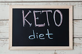 "Blackboard with text ""Keto Diet"" on wooden background, top view. Ketogenic diet concept, a new trend in slimming. Nutrition concept"