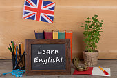 Learning languages concept - blackboard with text 'Learn English!', flag of the United Kingdom, books, pencils, compass on wooden background