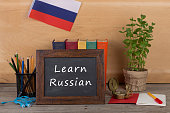 "Learning languages concept - blackboard with text ""Learn Russian!"", flag of the Russia, books, pencils, compass on wooden background"