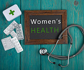 "Medecine concept - Blackboard with text ""Women's health"", stethoscope, pills on blue wooden background"