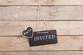 "Blackboards with text ""You're invited"" on wooden background"