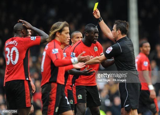 Blackburn Rovers' Christopher Samba is shown the yellow card by referee Mark Clattenburg after giving away a penalty