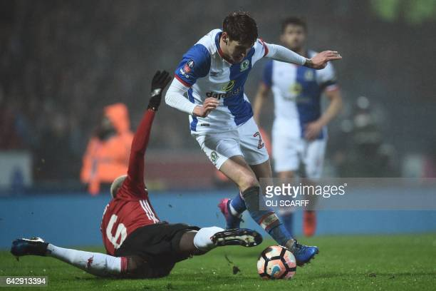 Blackburn Rovers' English midfielder Connor Mahoney is tackled by Manchester United's French midfielder Paul Pogba during the English FA Cup fifth...