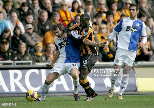 Blackburn Rovers' Gael Givet is fouled by Hull City's Bernard Mendy as they battle for the ball Blackburn Rovers' Roque Santa Cruz looks on