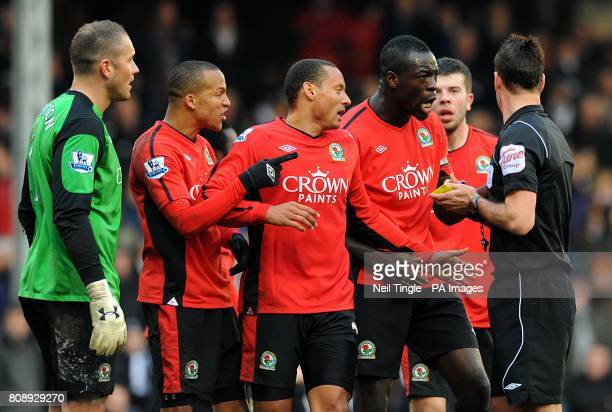 Blackburn Rovers' players including Christopher Samba argue with referee Mark Clattenburg after giving away a penalty