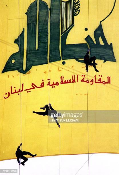 Blackclad Hezbollah militants descend in front of a giant banner reading 'Hezbollah the Islamic Resistance in Lebanon' 15 January in a southern...