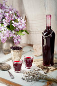 Blackcurrant homemade liquor on a wooden background with lilac flowers