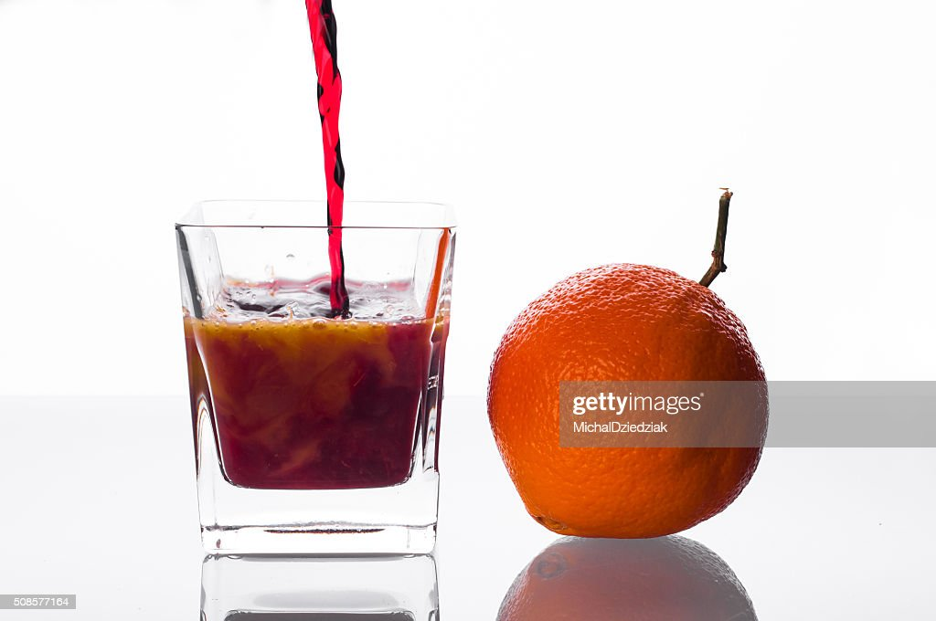 blackcurrant juice pouring into glass with orange juice : Stock Photo