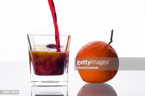 blackcurrant juice pouring into glass with orange juice : Stockfoto