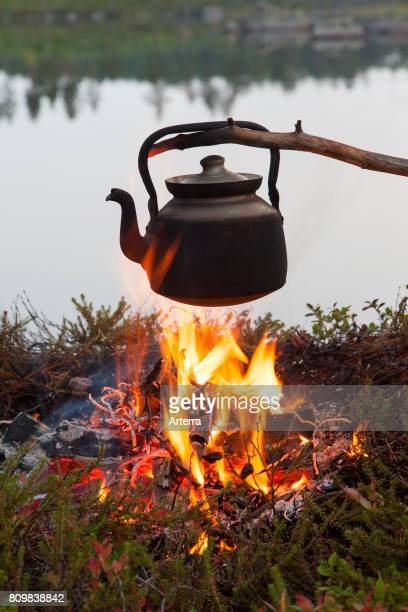 Blackened tin kettle boiling water over flames from campfire during hike along lake