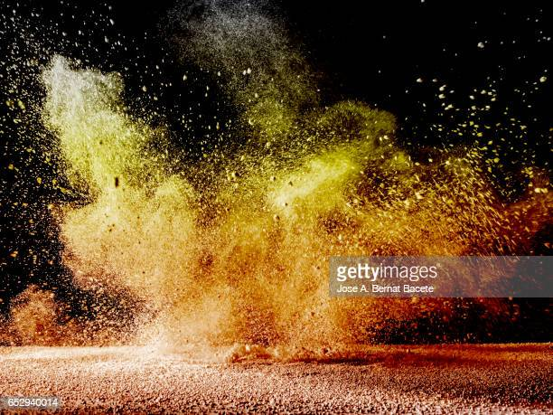 Blackground of particles of yellow and orange color powder in ascending movement floating in the air produced by an impact