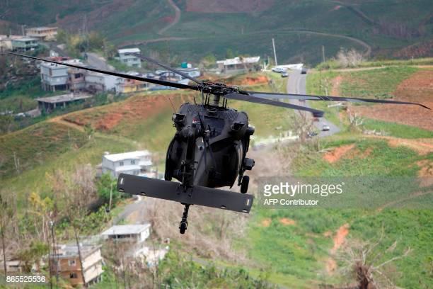 Blackhawk helicopter flies over Naranjito on its way to the town of Barranquitas with supplies for their residents affected by the passing of...