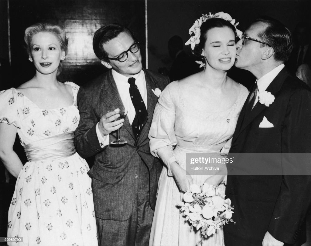 Blacklisted American playwright Sidney Kingsley (1906 - 1995, far left) kisses the cheek of American heiress and designer <a gi-track='captionPersonalityLinkClicked' href=/galleries/search?phrase=Gloria+Vanderbilt+-+Fashion+Designer&family=editorial&specificpeople=214786 ng-click='$event.stopPropagation()'>Gloria Vanderbilt</a> as American film director <a gi-track='captionPersonalityLinkClicked' href=/galleries/search?phrase=Sidney+Lumet&family=editorial&specificpeople=214143 ng-click='$event.stopPropagation()'>Sidney Lumet</a> and American actress Carol Grace (1925 - 2003) stand by during Lumet and Vanderbilt's wedding, August 28, 1956. Lumet holds a drink and Vanderbilt holds a bouquet of flowers.