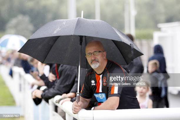 A Blackpool fan shelters from the rain under an umbrella